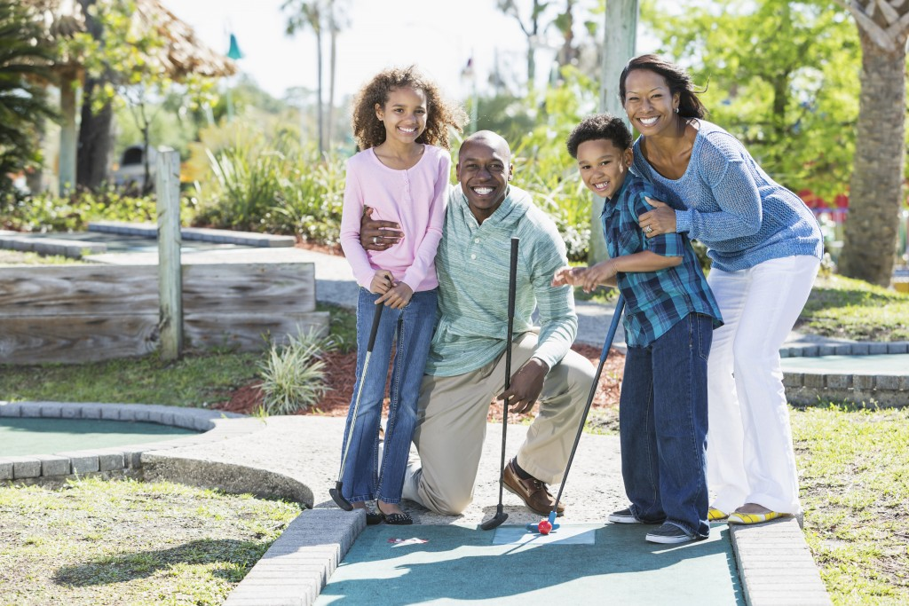 African American family with two children (6 and 9 years) at amusement park playing miniature golf.
